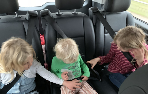The big sisters helping the little sister to fasten her seat belts in a Brussels taxi